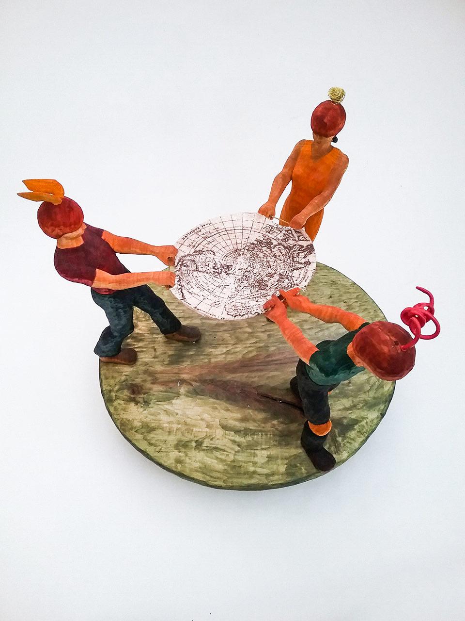 Skulptur aus Holz – drei Personen ziehen an Weltkarte