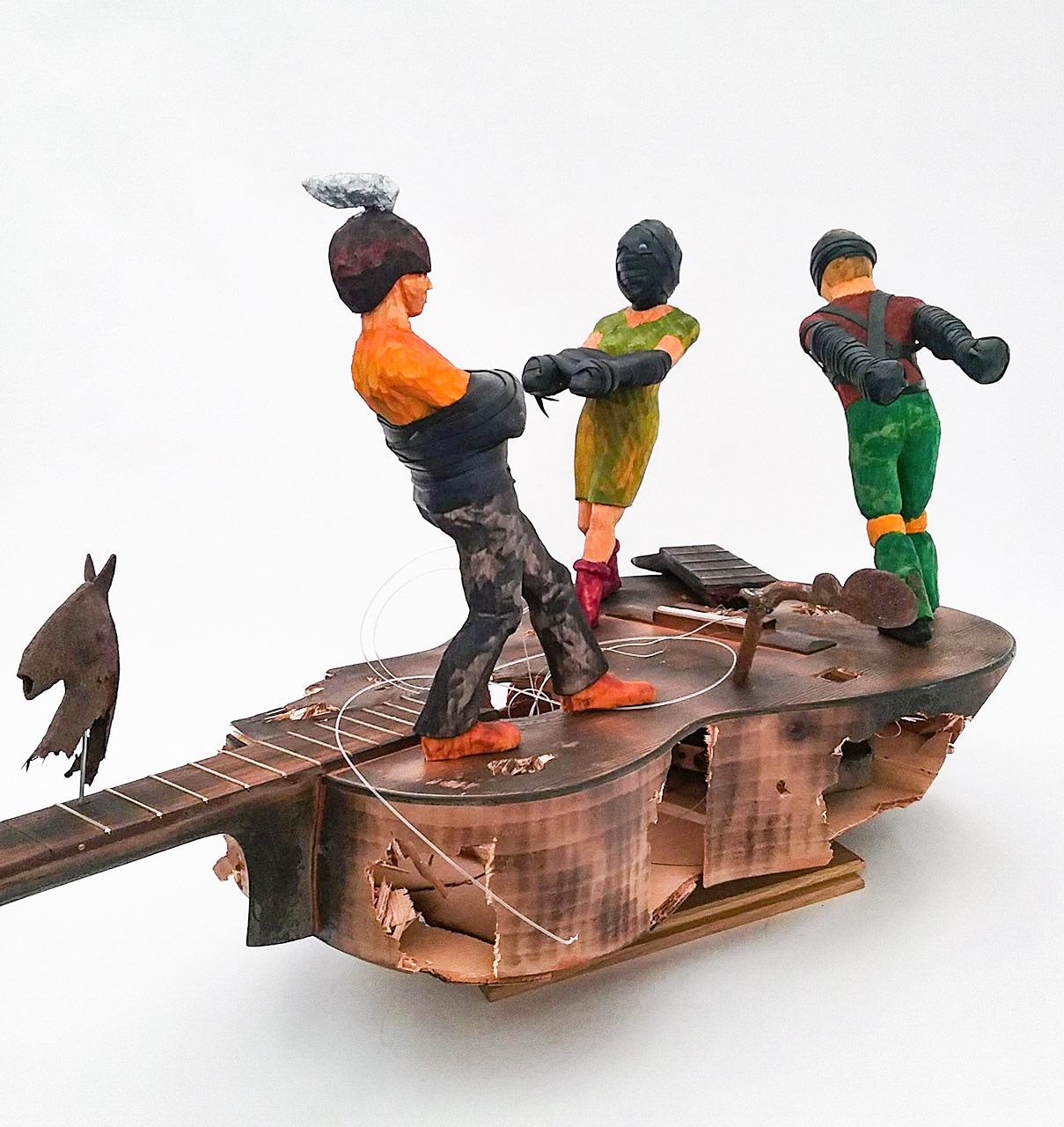 Holzskulptur: gefesselte Personen auf Geige