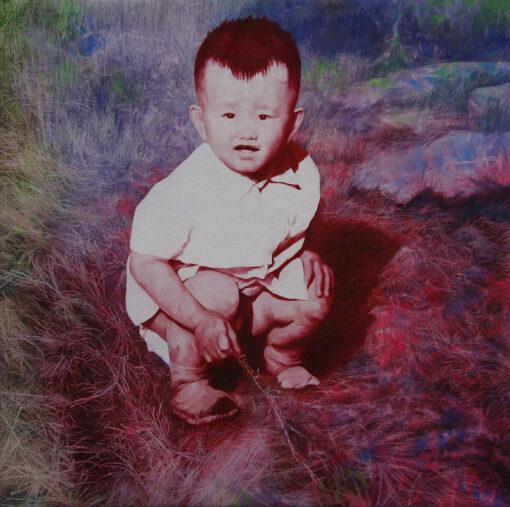 Bild eines jungen Kindes das im Gras sitzt und spielt