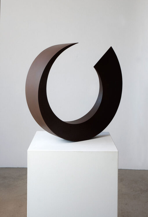 abstrakte Skulptur aus Cortenstahl, die einen fast geschlossenen Kreis bildet